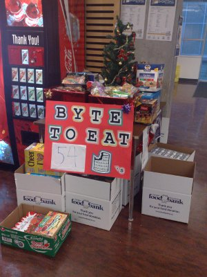 Table with Byte to Eat poster, donations, and Christmas tree